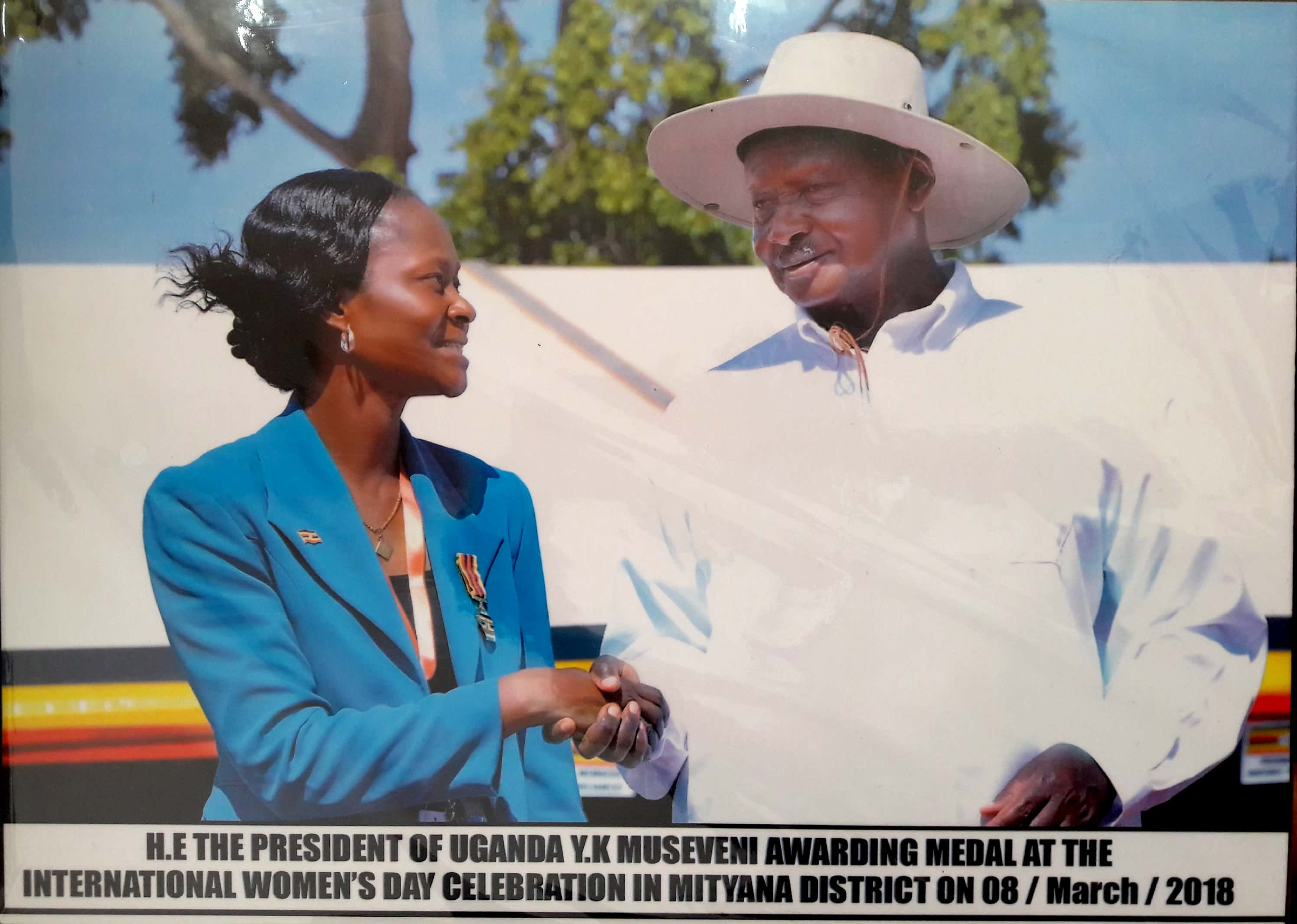 Dr. Robinah Kulabako shaking the hand of President Yoweri Museveni after receiving her National Medal on March 2018, International Women's Day.